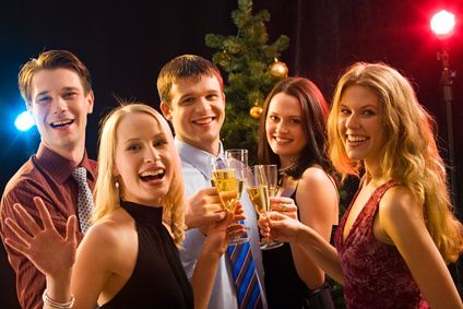 Smiling group of young people enjoying cocktails at christmas
